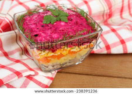 Russian herring salad in glass bowl on wooden table background - stock photo