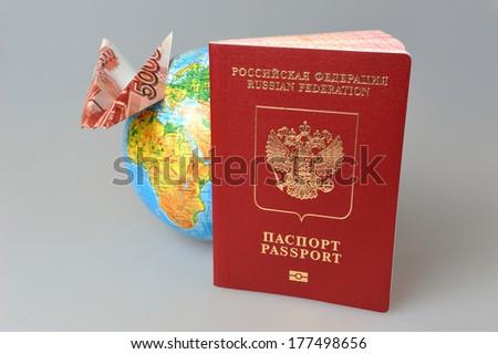 Russian International passport, globe and origami plane made from money on gray background - stock photo
