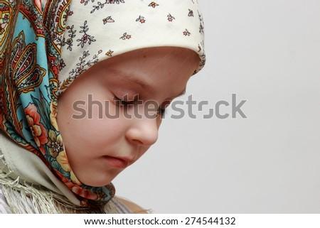 russian little girl in traditional skarf praying - stock photo