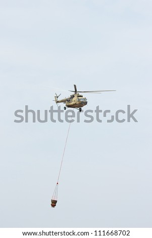 Russian military helicopter MI-8 extinguishes the fire with water in the cloudy sky - stock photo