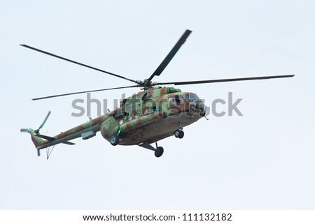 Russian military helicopter MI-8 in the cloudy sky - stock photo