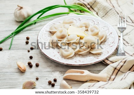 Russian national cuisine , cooked dumplings with meat, spices , green onions, pepper, salt and butter on a wooden background - stock photo