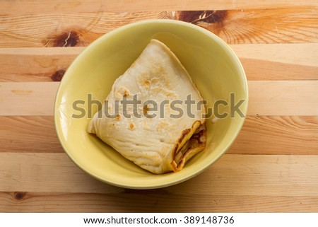 Russian national dish pancakes with condensed milk on a plate on wooden background