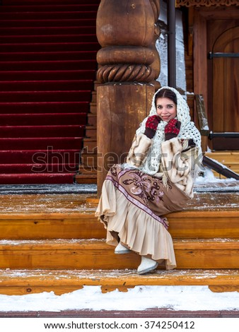 Russian noblewoman in Russian national winter clothes on the porch of the ancient Russian wooden Kremlin