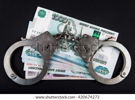 Russian Rubles and Handcuffs on the Black Background - stock photo