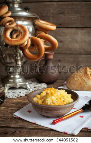 Russian rustic still life: a samovar with bagels, millet porridge with pumpkin, homemade bread and cherry jam. Selective focus. Toned. - stock photo
