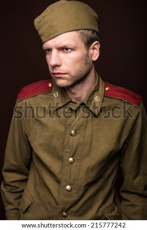 Russian soldier looks at something. Studio portrait isolated on brown background - stock photo