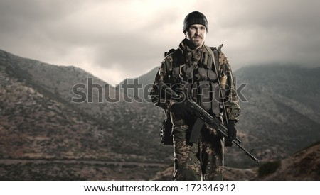 Russian soldier with a rifle. Steps against mountains. - stock photo