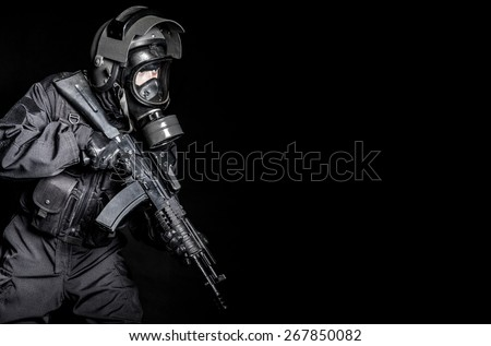 Russian special forces operator in black uniform and gas mask