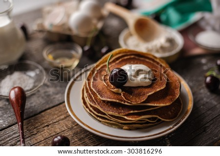 Russian style freshly baked pancakes with cherry - stock photo