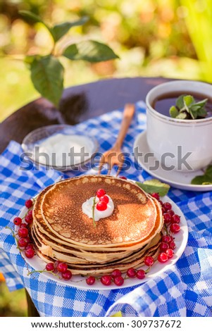 Russian style pancakes with redcurrants and mint tea outdoors - stock photo