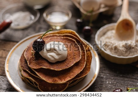 Russian style tasty pancakes with sour cream and berries - stock photo