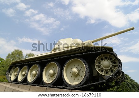 russian tank t34 on concrete basement in front of cloudy sky and forest - stock photo