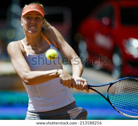 Russian tennis player Maria Sharapova returns a ball during a match of Mutua Madrid Open 2013 clay court ATP World Tour Masters 1000 tournament in Madrid, Spain at Caja Magica Venue on May 10, 2013  - stock photo