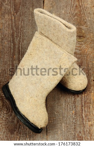 Russian traditional winter felt boot valenki on wooden background ...