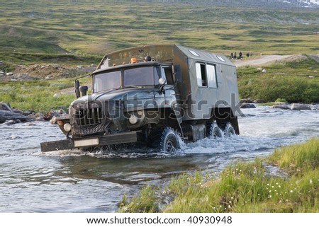 Russian truck Ural crossing a small river