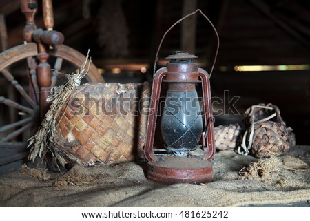 Russian vintage household items. Still life. Old spinning wheel, bast shoes and a kerosene lamp in a dusty garret in the country house. Selective focus.
