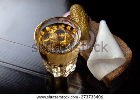 Russian vodka in small glass with black bread, pickled, onion and bit of lard on black background