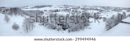 Russian winter. Snow-covered landscape with the village of Kruppsk next to the Izborsk Fortress near Pskov, Russia. - stock photo
