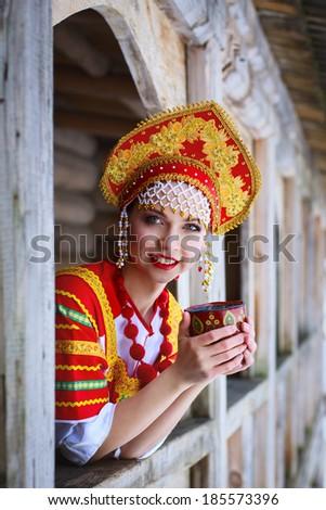 Russian woman in a kokoshnik a smiling in a village - stock photo