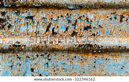 Rust flaking paintwork on old corrugated metal surface - stock photo