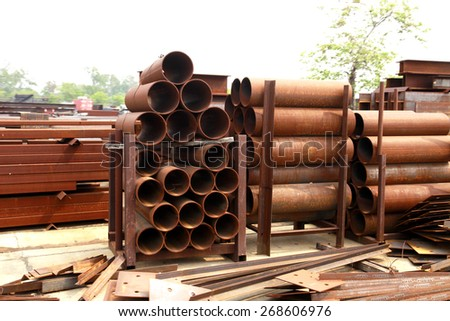 Rust steel pipes & steel angles in warehouse - stock photo