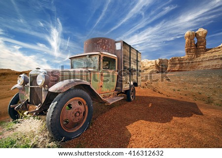 rusted abandoned truck in a rocky desert landscape - stock photo