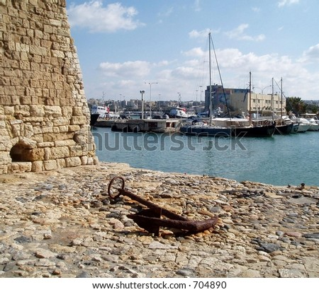 Rusted Anchor with Heraklion Venetial Harbor Background