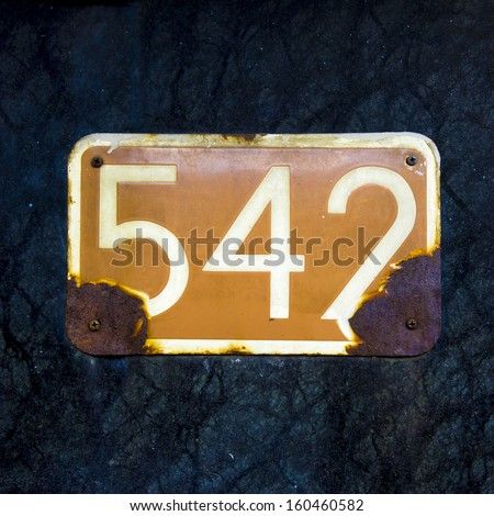 rusted and weathered house number five hundred and forty two - stock photo