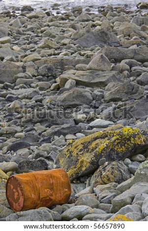 Rusted chemical drum washed ashore at high tide on the Cornish coast UK - stock photo