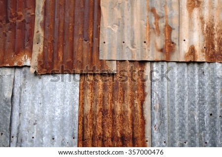 Rusted corrugated zinc sheets overlapping to form a fence - stock photo