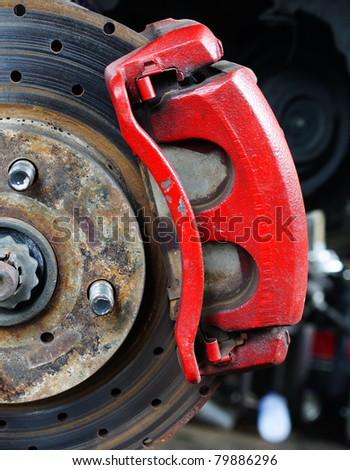 Rusted disc brake and caliper on car - stock photo