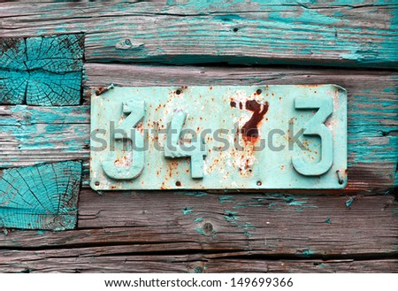 Rusted house number on grunge green wooden wall - stock photo