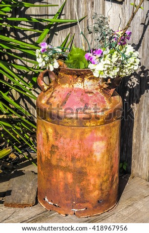 rusted metal milk can decorated with flowers - stock photo