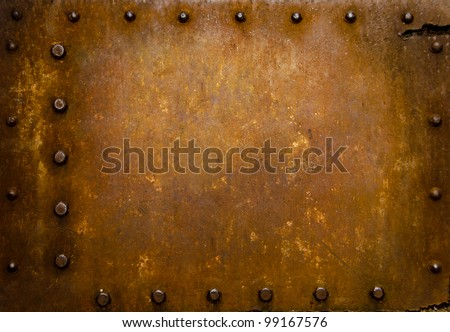 Rusted metal wall plate with three borders of metal studs, showing orange and brown scratch and scuff marks.  Suitable for wallpaper or background or grunge texture. - stock photo