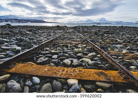 Rusted old rails to the sea - stock photo