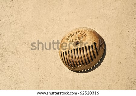 Rusted sprinkler alarm on building wall outside. - stock photo