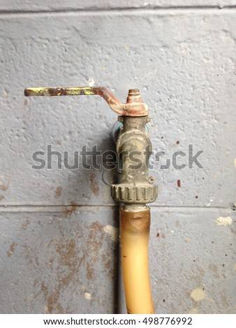 rusted water tap conected with rubber hose. Behind is old grey wall