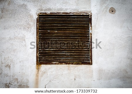 rustic air vent window on a grungy wall - stock photo