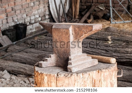 Rustic anvil on wooden stump. - stock photo