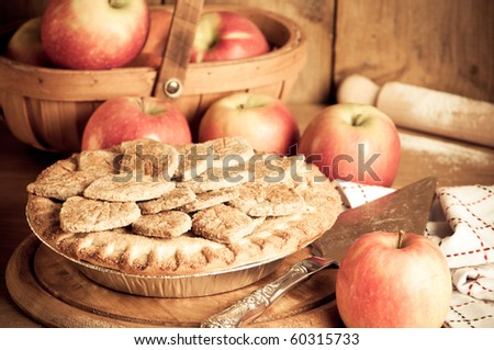 Rustic apple pie prepared with ripe apples for Thanksgiving in kitchen setting - stock photo
