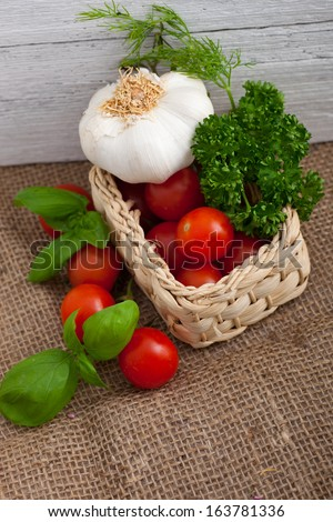 Rustic arrangement of ripe fresh tomatoes, a whole garlic bulb and herbs, including basil, dill and parsley, in a wicker basket on a burlap background - stock photo