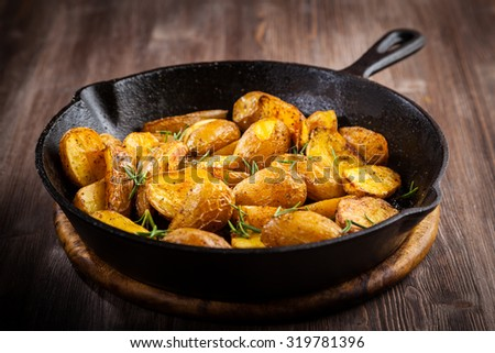 Rustic baked potatoes withherbs in a pan - stock photo