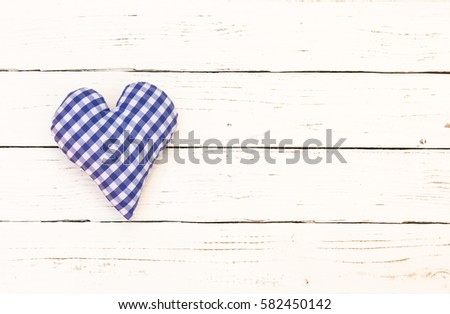 Rustic blue heart on white wood background.