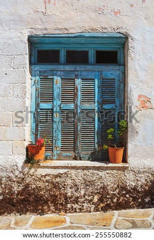 Rustic blue window and flower pots in Halki village, Naxos Island, Greece. - stock photo