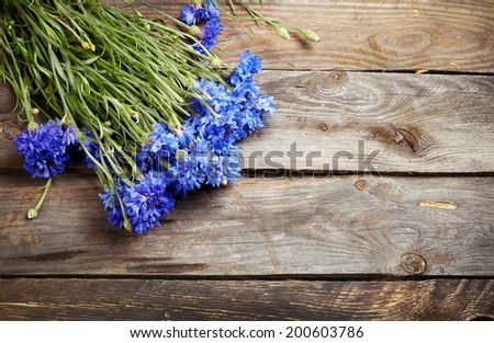 Rustic bouquet of blue cornflowers on vintage wooden board - stock photo