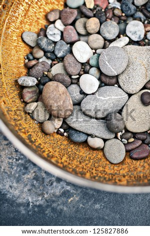 Rustic bowl of gathered river stones.