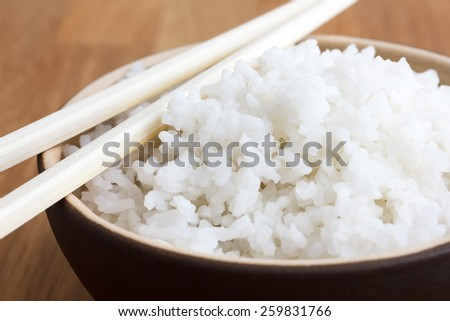 Rustic bowl of white rice on modern wood surface. With chopsticks. - stock photo