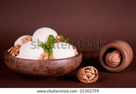 Rustic bowl with vanilla ice cream and fresh walnuts - stock photo