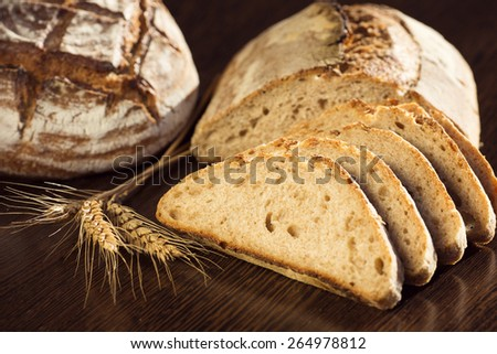 Rustic bread and wheat on a dark brown fundal - stock photo